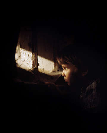 peeking: Girl looking out window and crying Stock Photo