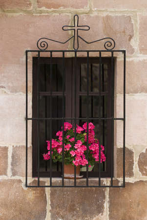 grates: Window with flowers and cross, Carmona, Cantabria, Northern Spain   Stock Photo