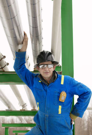 eyecontact: Industrial worker standing under piping