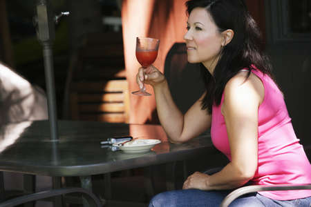 Woman drinking on patio Stok Fotoğraf