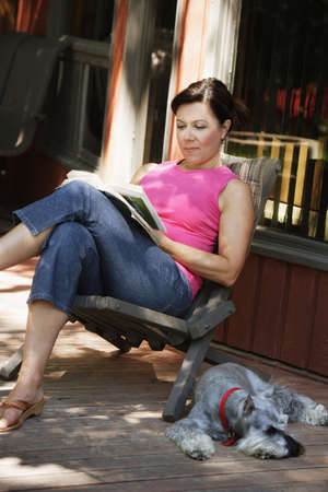 one mid adult woman only: Woman reading outside with dog