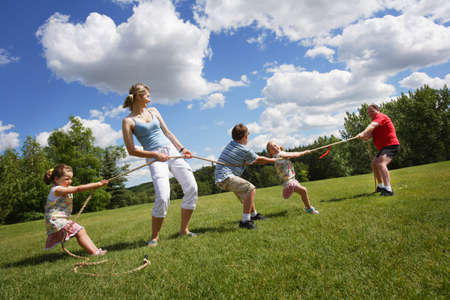 Tug of war between dad and mom with kids photo