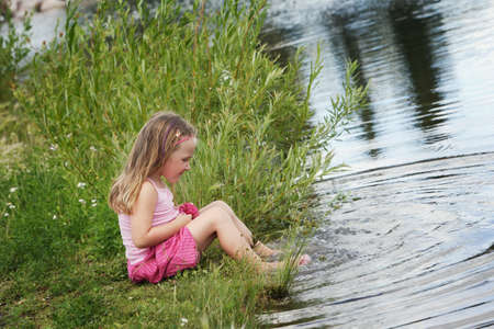 with reflection: Child playing by the water Stock Photo