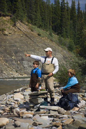 Vader en kinderen op de oever van de rivier