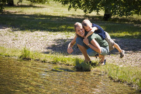 thirty���s: Mother giving son piggyback near lake