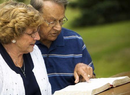 Senior paar lezen van de Bijbel  Stockfoto