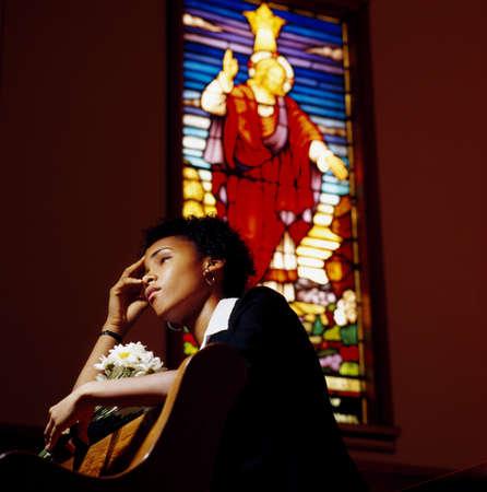 A sad woman in a church Imagens