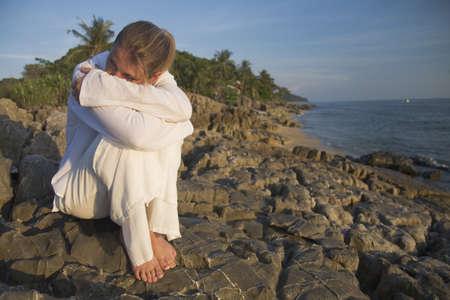 uncomfortable: Woman on rocky shoreline