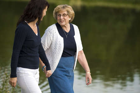 dos personas conversando: Dos mujeres caminando al lado de un lago