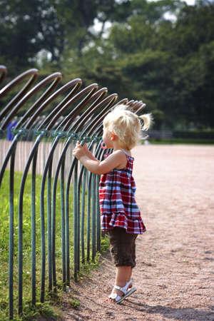 Meisje staan tegen een hek in een park  Stockfoto