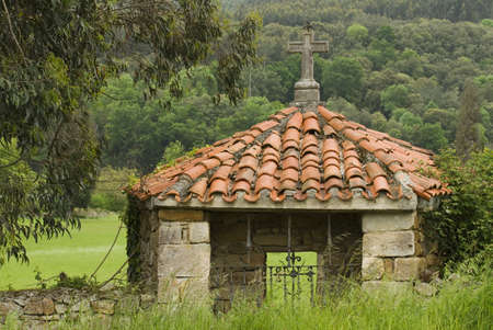 Pantiled roof shrine with stone cross in Rioseco, Northern Spain