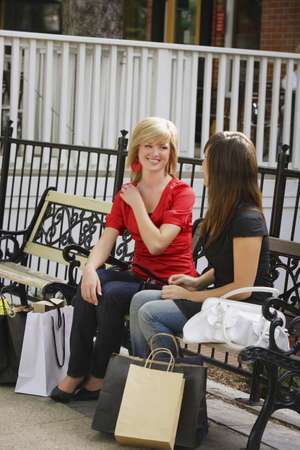 glubish: Friends sitting on a bench after shopping Stock Photo