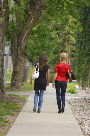 sidewalk talk: Friends walking on the sidewalk Stock Photo