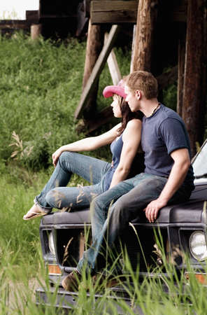 countryside loving: Couple sitting on the hood of a vehicle