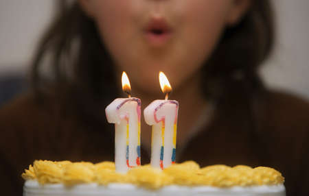 occasions: Girl blowing out candles on a birthday cake Stock Photo