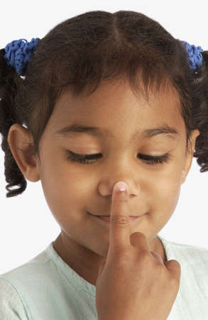 touching noses: Girl touching her nose