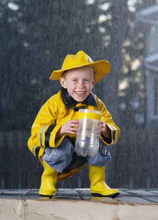 botas de lluvia: Ni�o bajo la lluvia  Foto de archivo