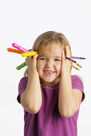 creativeness: A girl holding crayons and markers