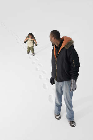 Boy following dad in the snow photo