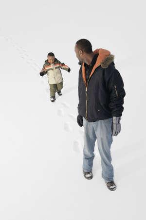 seguito: Ragazzo, seguendo le orme del padre nella neve  Archivio Fotografico