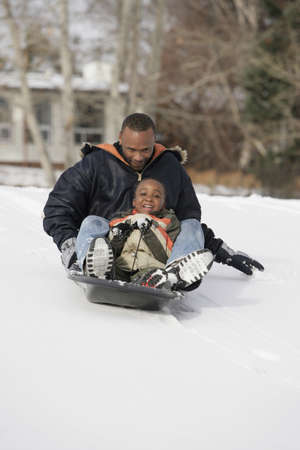family unit: Father and son sledding on snow