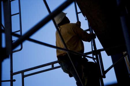 scaling ladder: Construction worker climbing