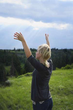belief systems: Ragazza con le mani sollevate verso il cielo