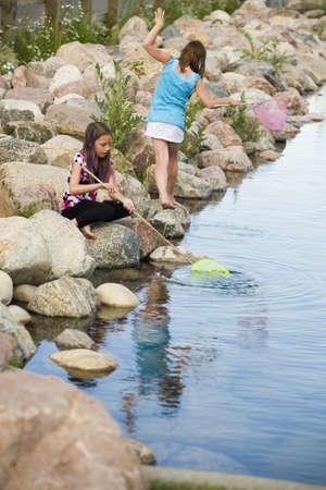 ni�as jugando: Dos ni�as jugando por el agua  Foto de archivo