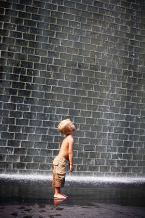 unrestrained: A boy standing beside a wall fountain, Chicago, Illinois, USA Stock Photo