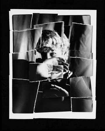 Torn up photo of child blocking face with hand Stockfoto
