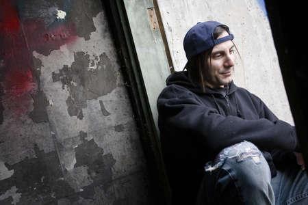 hombre sucio: Hombre sentado desgastado fuera ropa