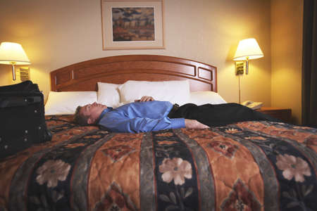 A man laying on a bed in a hotel room Stock Photo - 7206957