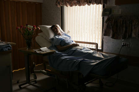 hardships: Man in a hospital bed Stock Photo