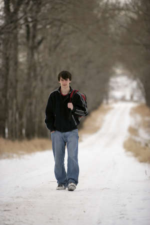 A teenage boy walking on a snow-covered path Reklamní fotografie