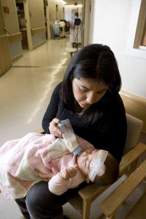 Woman bottle feeding baby girl photo