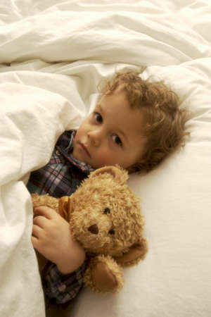 bed time: Boy laying in bed with teddy bear
