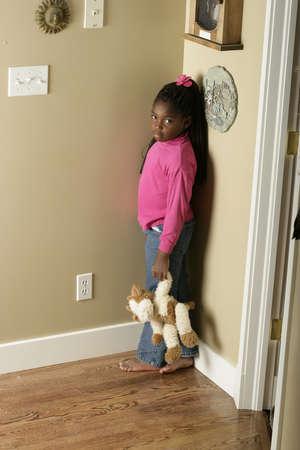 disciplina: Chica de pie en la esquina  Foto de archivo