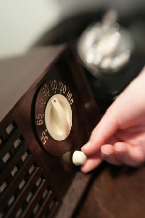 historical periods: Woman changing dial on old radio Stock Photo