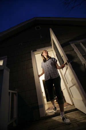 frightfulness: Woman stepping out of a house Stock Photo