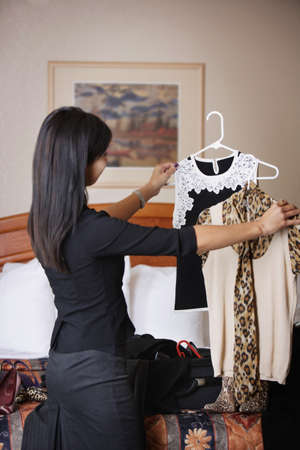 hotel bedroom: A woman comparing outfits