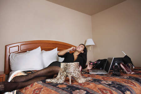 Woman on phone surrounded by shoes photo