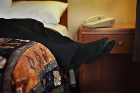 男性の足がベッドからぶら下がっています。