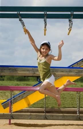 Girl swinging on monkey bars   免版税图像