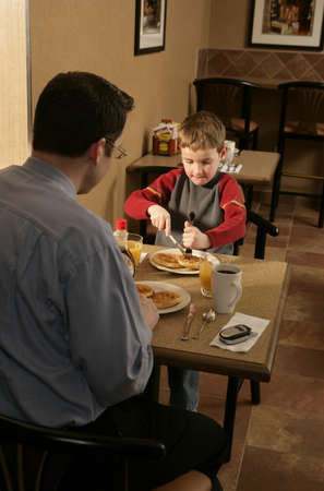 family units: Father and son at eating breakfast