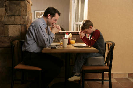 belief system: Father and son praying before meal