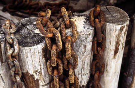 oxidado: Cadenas oxidadas en puestos de madera  Foto de archivo