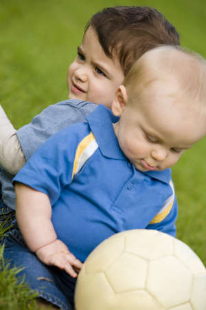 Infant and toddler with soccer ball photo