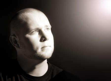 Portrait of man looking towards a light photo
