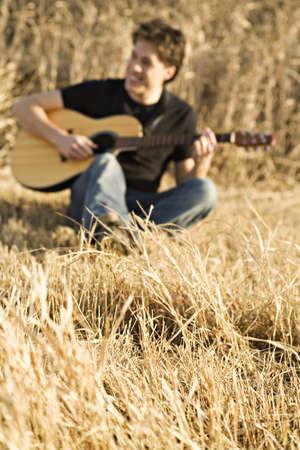 alabanza: Hombre tocando la guitarra en campo  Foto de archivo