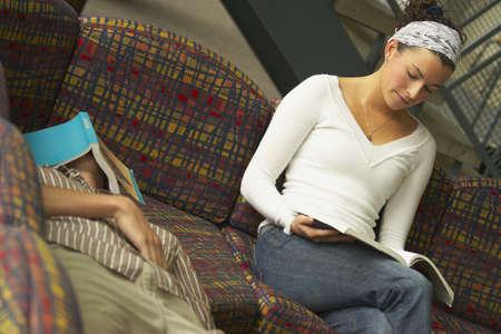 bookish: Woman reading and man sleeping